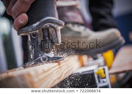 construction worker sawing a plank of wood stock photo © photography33