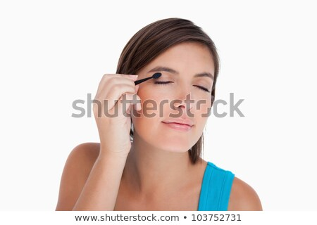 Beautiful teenager applying eyeshadow in a determined way Stock photo © wavebreak_media