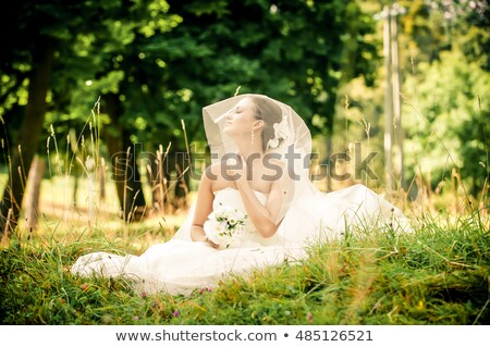 Young beautiful bride sitting at a forest glade Stock photo © pzaxe