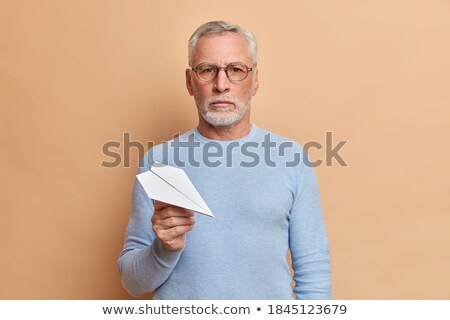 concentrated businessman looking at paper airplane stock photo © rugdal