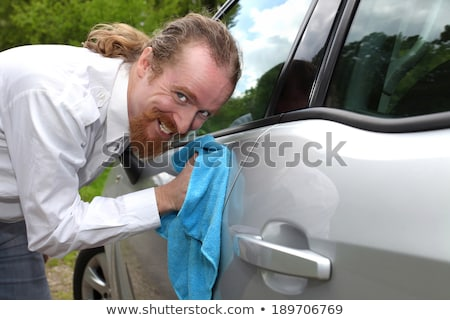 Portrait of funny man washing car with a cloth Stock photo © vladacanon