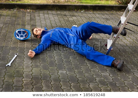 Young Unconscious Technician Lying On Street Stock photo © AndreyPopov
