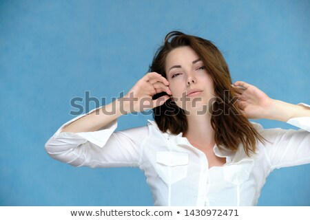portrait of happy girl with long dark blowing hair against blue stock photo © gromovataya