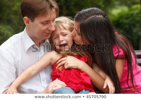 Parents calm crying girl on walk in summer garden. Girl sits in lap at father. Stock photo © Paha_L