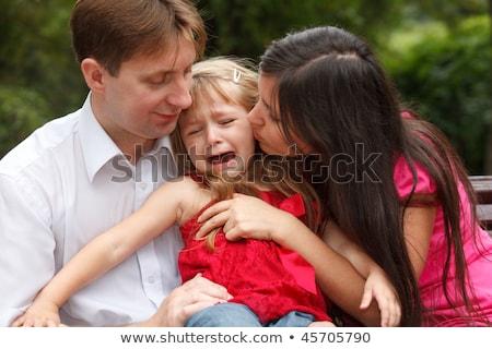 ストックフォト: Parents Calm Crying Girl On Walk In Summer Garden Girl Sits In Lap At Father