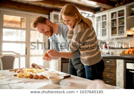 lovely smiling young woman making pasta in kitchen stock photo © deandrobot