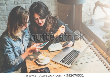 Girl friends sitting together in cafe and showing photos on smar Stock photo © Kzenon