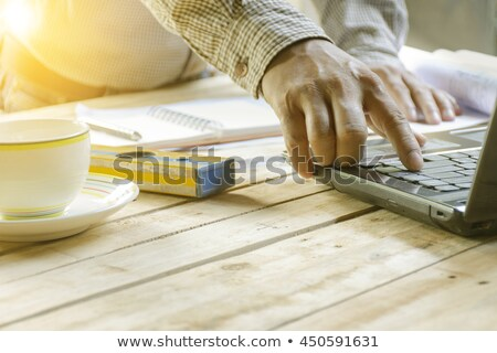 Young architects working his laptop with equipment construction on wooden table. stock photo © Bigbubblebee99