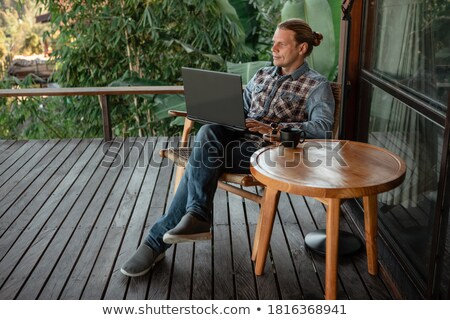 Young man in casual clothes drinks coffee while sitting in a caf Stock photo © artsvitlyna