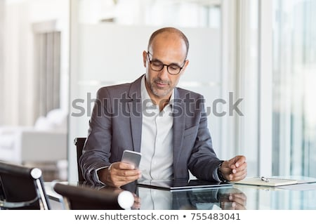 executives using mobile phone laptop and digital tablet in the office stock photo © wavebreak_media