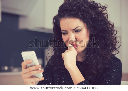 picture of confused woman with smartphone stock photo © dolgachov