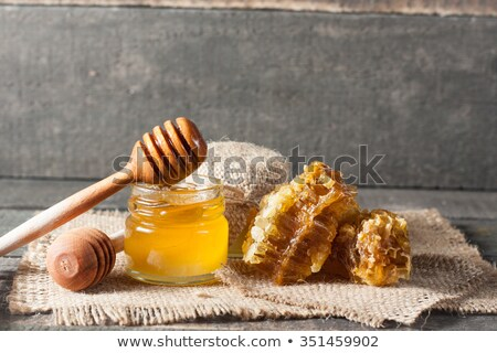 Organic honey drips from wooden dipper in jar Stock photo © FreeProd