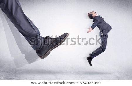 Black shoe kicking small man Stock photo © ra2studio