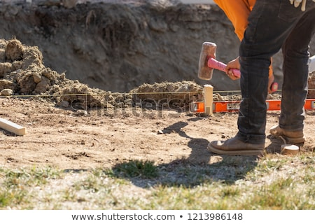 Worker Installing Stakes and Lumber Guides At Construction Site Stock photo © feverpitch
