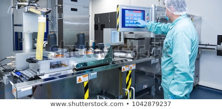 Stockfoto: Pharmacy Industry Factory Man Worker In Protective Clothing In Sterile Working Conditions