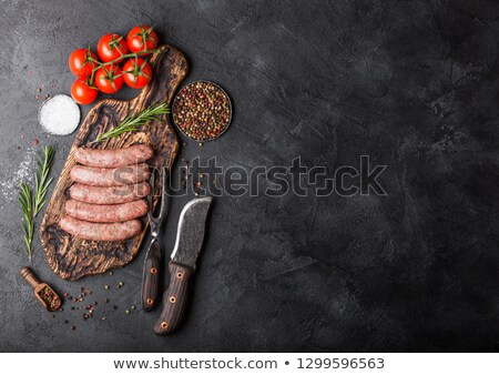Raw beef and pork sausage on old chopping board with vintage knife and fork on black background.Salt Stock photo © DenisMArt