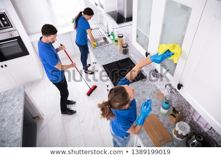 Male Janitor Cleaning Oven With Napkin Stock photo © AndreyPopov