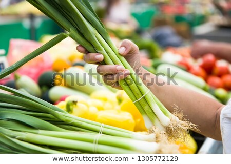 Woman buying bunches of spring onions on stall at the market Stock photo © boggy