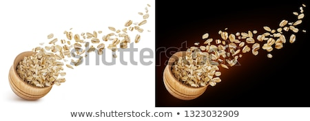 Oat flakes flying out of wooden bowl isolated on white and black background Stock photo © xamtiw