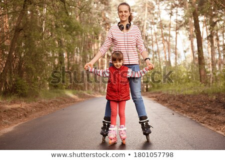 Two happy young girls on on roller skates spending time Stock photo © deandrobot
