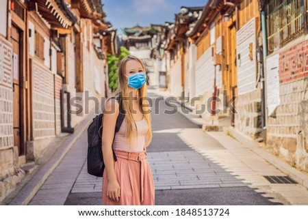Young woman tourist in medical mask in Bukchon Hanok Village is one of the famous place for Korean t Stock photo © galitskaya