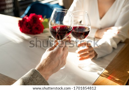 Stock photo: Hands with red wine toasting over served table with food.