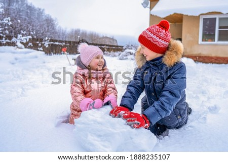 Boy and Girl Sculpting Snowman from Snow in Park Stock photo © robuart