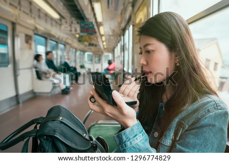 Girl putting on make-up (lip stick) Stock photo © IS2