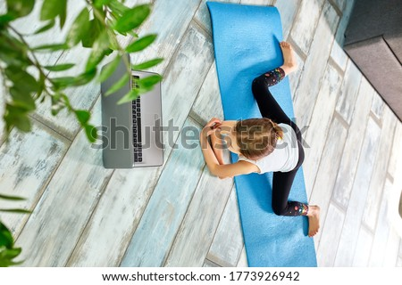 Little girl make workout on blue mat at home by laptop online. Stock photo © Illia