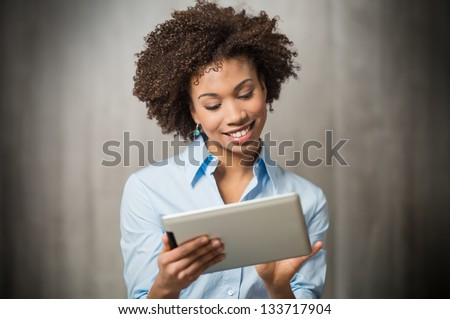 Positive successful woman entrepreneur with Afro hair holds digital tablet, stands outdoor near offi Stock photo © vkstudio