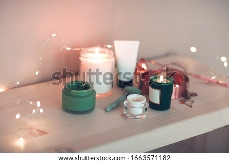 Burning candles and containers with various skincare cosmetics  Stock photo © dashapetrenko
