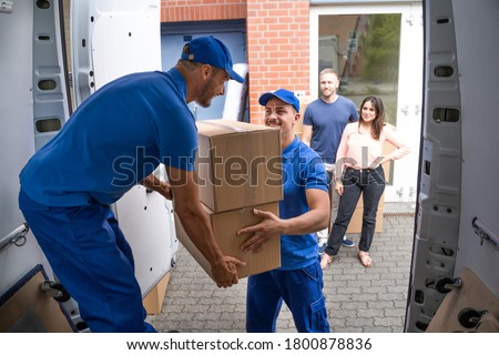Happy Family Couple Watching Movers Unload Boxes Stock photo © AndreyPopov