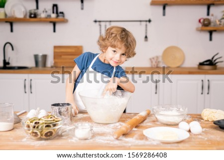 Cute and funny little boy pointing into bowl while going to make dough Stock photo © pressmaster
