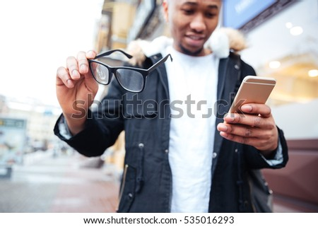 Image of african american man looking at camera while standing over wall Stock photo © deandrobot