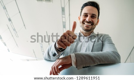 smart smiling business man shows thumbs up sign Stock photo © meinzahn