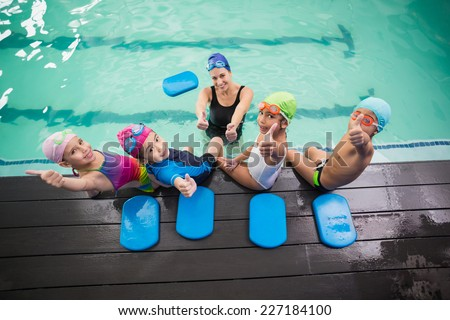 Stock photo: Male instructor swimming for children teaches a happy boy to swim in the pool