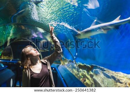 young woman looking at fish in a tunnel aquarium stock photo © galitskaya