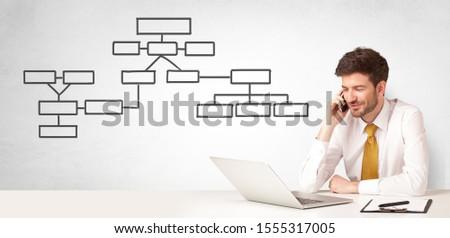 A salesman sitting at desk presenting organizational chart Stock photo © ra2studio