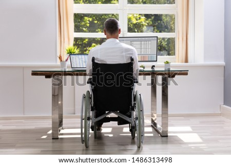 Young man in a wheelchair using a computer in the workplace Stock photo © photography33