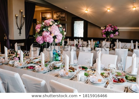 A composition of flowers and green is on a festive table at the wedding banquet hall. Stock photo © ruslanshramko