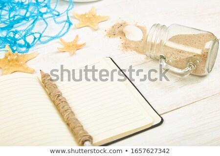 notebook with pencil and seashells on beach sand Stock photo © dolgachov