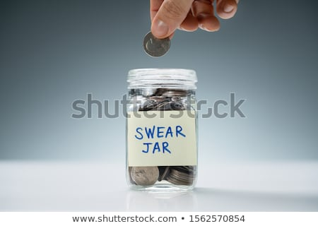 Person Inserting Coin In Swear Jar Over White Desk Stock photo © AndreyPopov