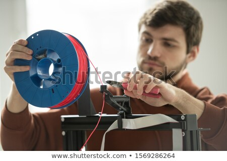 Young designer with nippers holding spool with red filament while cutting it Stock photo © pressmaster