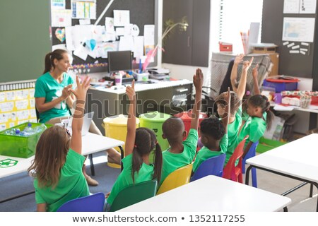 Front view of caucasian teacher and multi ethnic student discussing about green energy in classroom. Stock photo © wavebreak_media