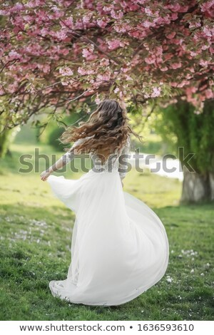 The bride a young woman in a long white dress whirls and dances in a spring Park Stock photo © ElenaBatkova