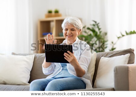 senior woman having video call on tablet computer Stock photo © dolgachov