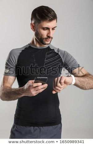 Kép brutális sportoló mobiltelefon izolált szürke Stock fotó © deandrobot