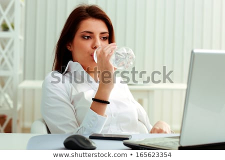 Stock photo: Office worker drinking water at her desk