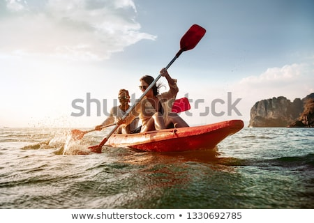 Stock photo: Man on Paddleboard Woman on Kayak