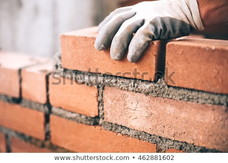 Stock photo: bricklayer with brick on construction site